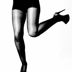 Ben i svart strømpebukse og høye hæler, ett ben opp bakover