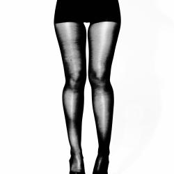 Ben i svart strømpebukse og høye hæler, rett forfra, elegant